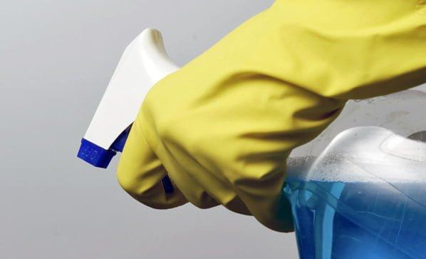 Hand in yellow glove holding spray bottle
