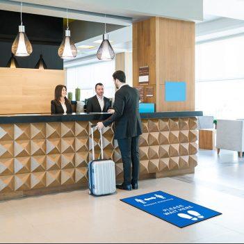 social distancing floor mat at hotel reception